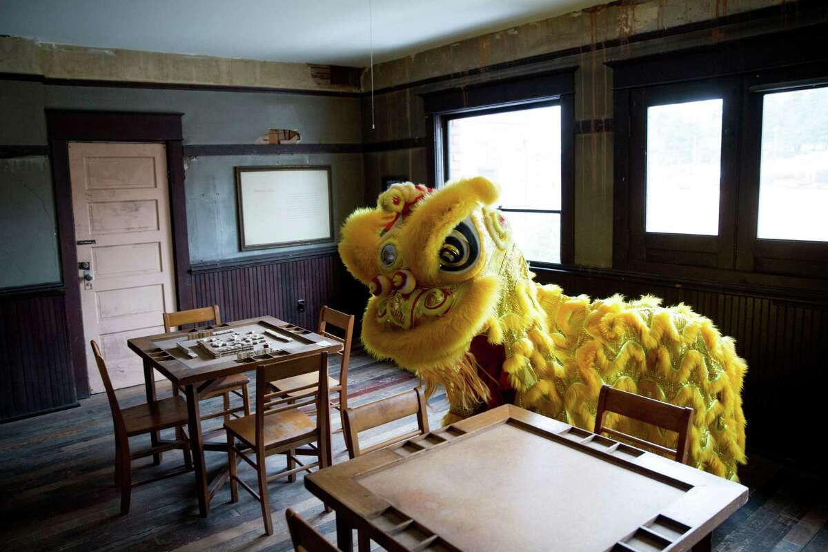 A lion from the LQ Lion Dance group blesses the historic spaces above the Wing Luke Museum of the Asian Pacific American Experience in the International District on Saturday, Feb. 6, 2016.