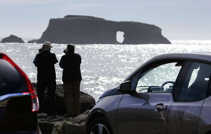 Local resident Hameed Qabazard (left) and Paul Rosenblum photograph the scenic view, which includes Arched Rock, from the Goat Rock parking lot at Sonoma Coast State Park in Bodega Bay, Calif. on Saturday, Feb. 6, 2016. State parks officials are seeking permission from the California Coastal Commission to charge day use fees in a number of parking lots along the Sonoma County coastline.