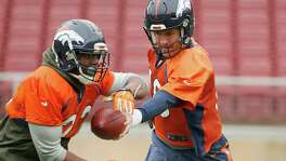 STANFORD, CA - FEBRUARY 03:  Peyton Manning #18 hands the ball off to C.J. Anderson #22 of the Denver Broncos during the Broncos practice for Super Bowl 50 at Stanford University on February 3, 2016 in Stanford, California. The Broncos will play the Carolina Panthers in Super Bowl 50 on February 7, 2016.  (Photo by Ezra Shaw/Getty Images)