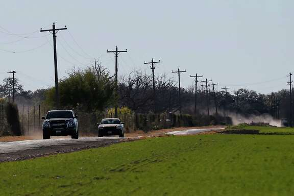 Uvalde County Sheriffs Department vehicles travel along a road which leads to a neighborhood several miles outside of Uvalde where a standoff resulted in multiple deaths on Saturday, Feb. 6, 2016. The incident started around 5 p.m. on Friday. Officials have not given an official account about the circumstances surrounding the standoff.  (Kin Man Hui/San Antonio Express-News)