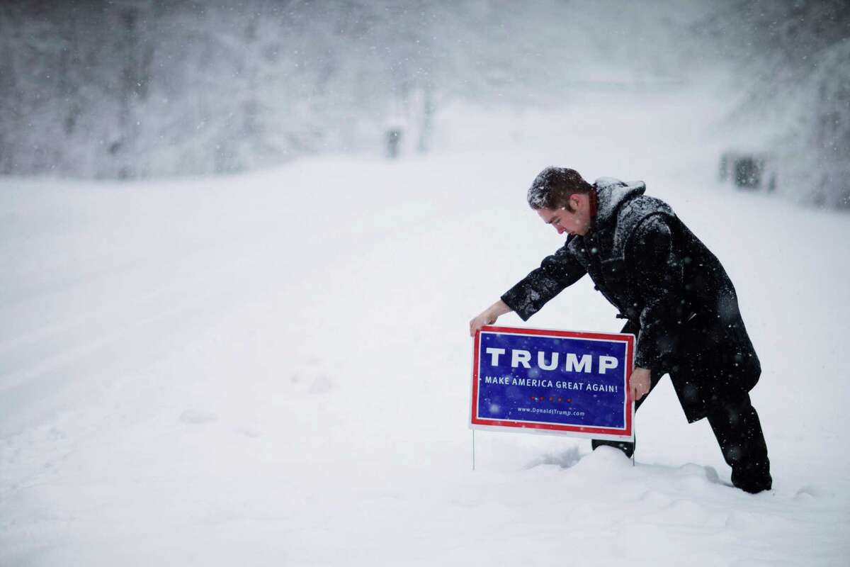 James Radcliffe, a volunteer for Republican presidential candidate Donald Trump, places a sign outside a home while walking through the snow knocking on doors in search of Trump supporters Friday, Feb. 5, 2016, in Londonderry, N.H. The twenty-two year old, from out-of-state who's never been involved in politics, is on the front lines of Trump'€™s ground war in New Hampshire, where the billionaire businessman is under intense pressure to win big. (AP Photo/David Goldman)