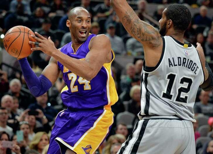 Los Angeles Lakers guard Kobe Bryant (24) attempts to pass around San Antonio Spurs forward LaMarcus Aldridge during the first half of an NBA basketball game, Saturday, Feb. 6, 2016, in San Antonio. (AP Photo/Darren Abate)