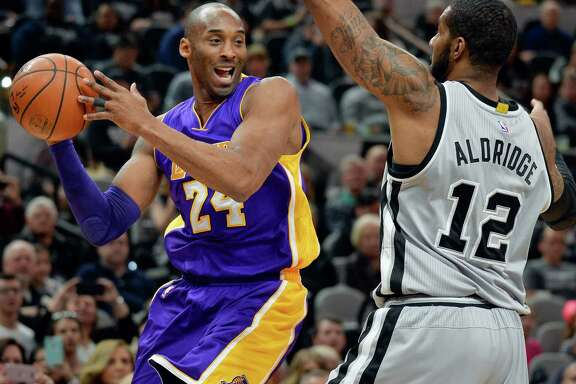 Los Angeles Lakers guard Kobe Bryant (24) attempts to pass around San Antonio Spurs forward LaMarcus Aldridge during the first half of an NBA basketball game, Saturday, Feb. 6, 2016, in San Antonio. (AP Photo/Darren Abate)