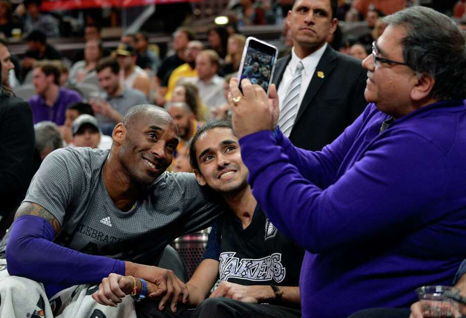 Los Angeles Lakers guard Kobe Bryant, left, poses for a photo with a fan during the first half of an NBA basketball game against the San Antonio Spurs, Saturday, Feb. 6, 2016, in San Antonio. (AP Photo/Darren Abate) Photo: Darren Abate, Associated Press / FR115 AP
