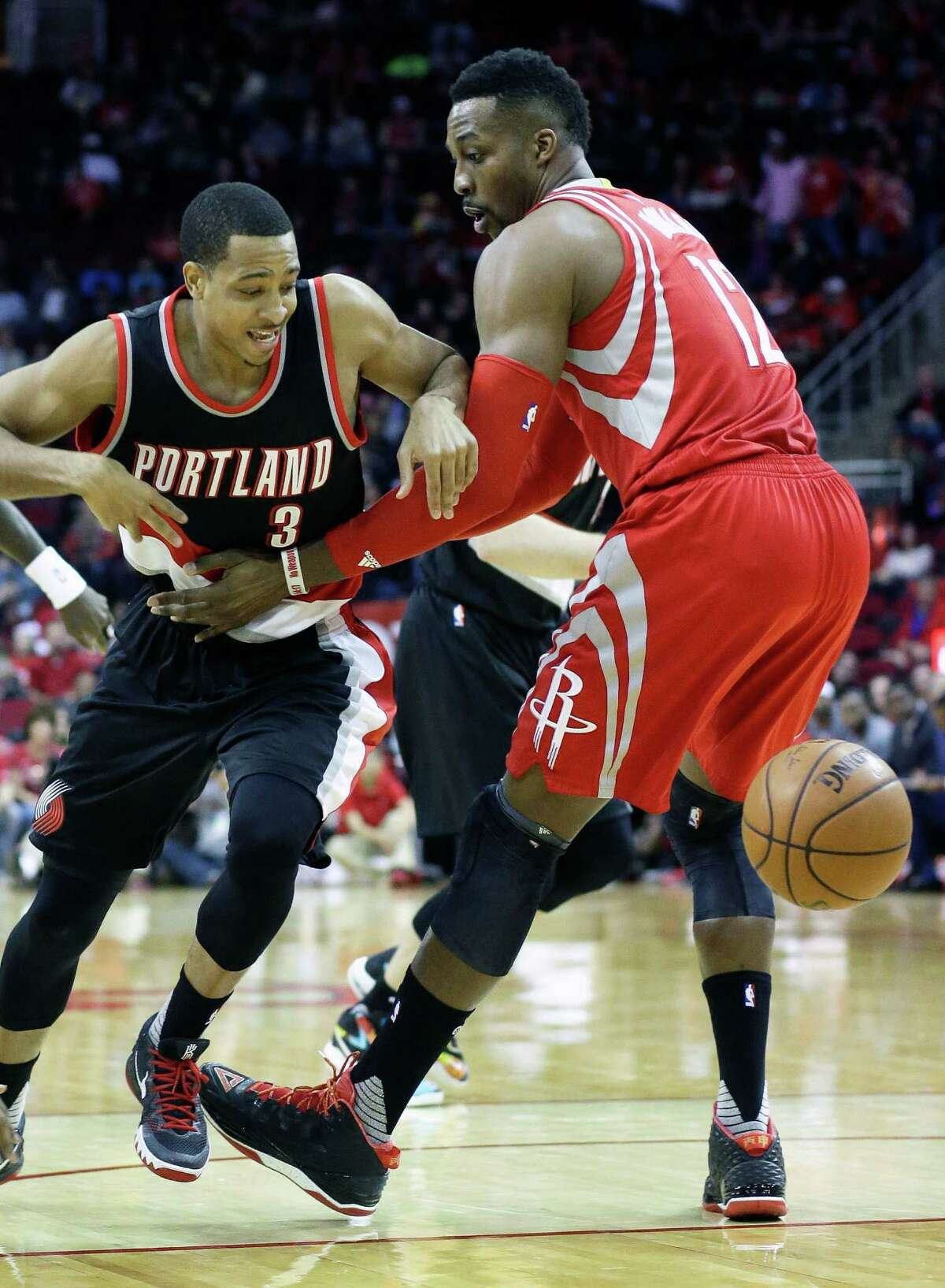 Portland Trail Blazers' C.J. McCollum (3) loses the ball with help from Houston Rockets' Dwight Howard (12) in the first half of an NBA basketball game Saturday, Feb. 6, 2016, in Houston. (AP Photo/Pat Sullivan)