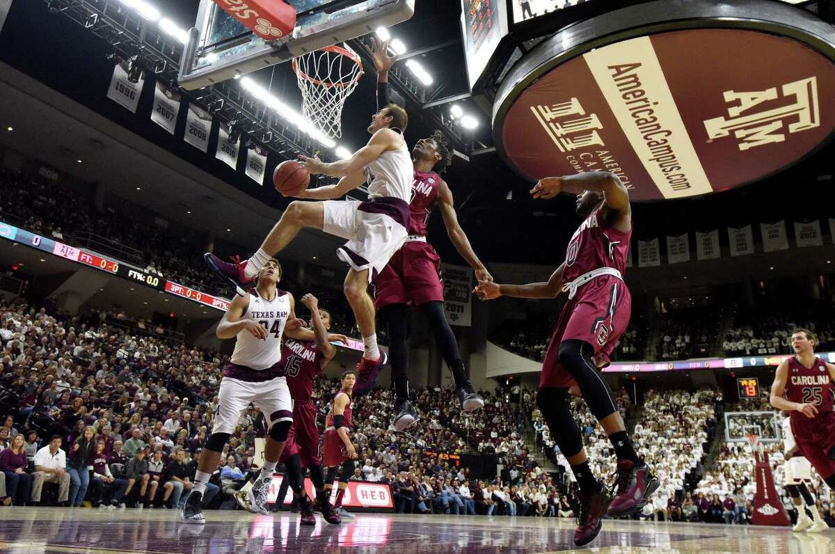 Texas A&M's Alex Caruso makes a basket as South Carolina's Chris Silva (30) defends during the first half of an NCAA college basketball game, Saturday, Feb. 6, 2016, in College Station, Texas. South Carolina won 81-78. (AP Photo/Sam Craft)