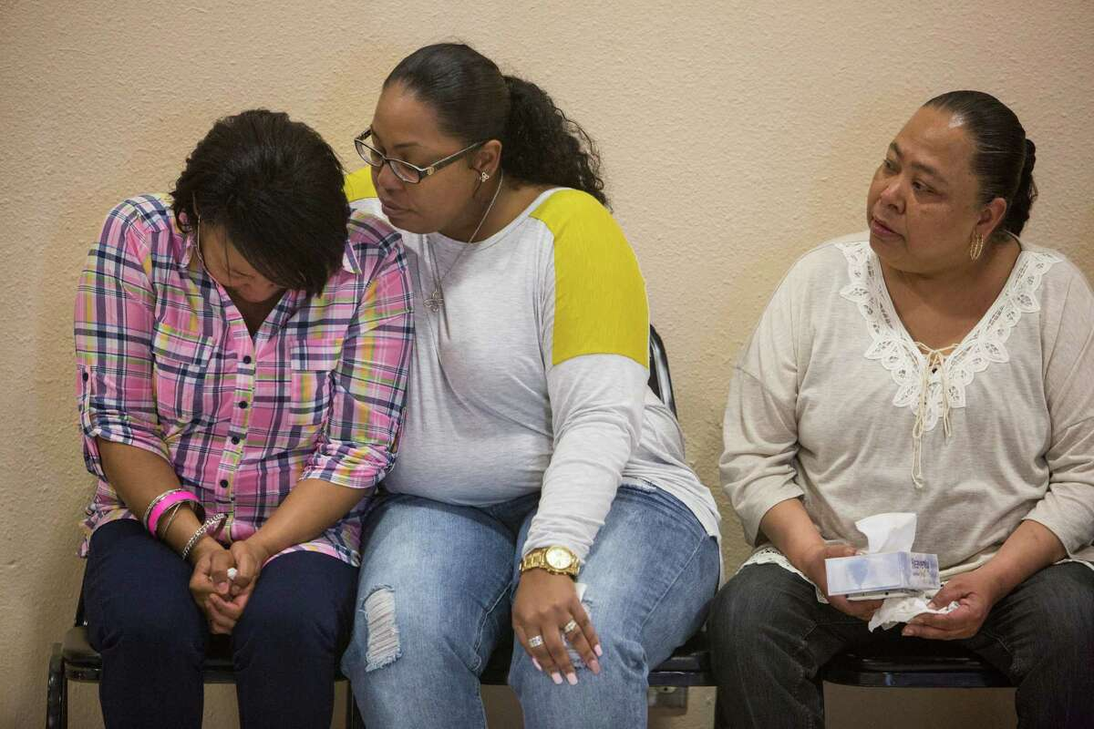 Charissa Sprawling-Mickles, center, comforts her sister Elena Sprawling-Scott during a press conference held at the Barbara Jordan Community Center about Antronie Scott's death in San Antonio, Texas on February 6, 2016. Scott, who was unarmed, was shot and killed by a San Antonio police officer outside of his car on Thursday evening as his wife Elena Sprawling-Scott watched from the passenger seat.