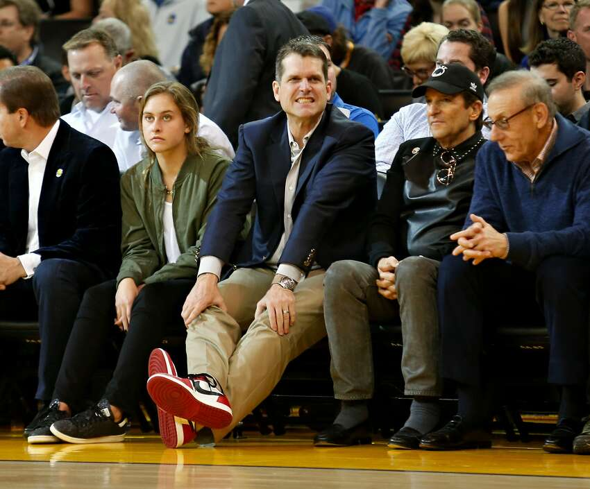 Former 49ers head coach Jim Harbaugh watches during the first quarter of the basketball game between the Golden State Warriors and the Oklahoma City Thunder on Saturday, February 6, 2016 in Oakland, Calif.