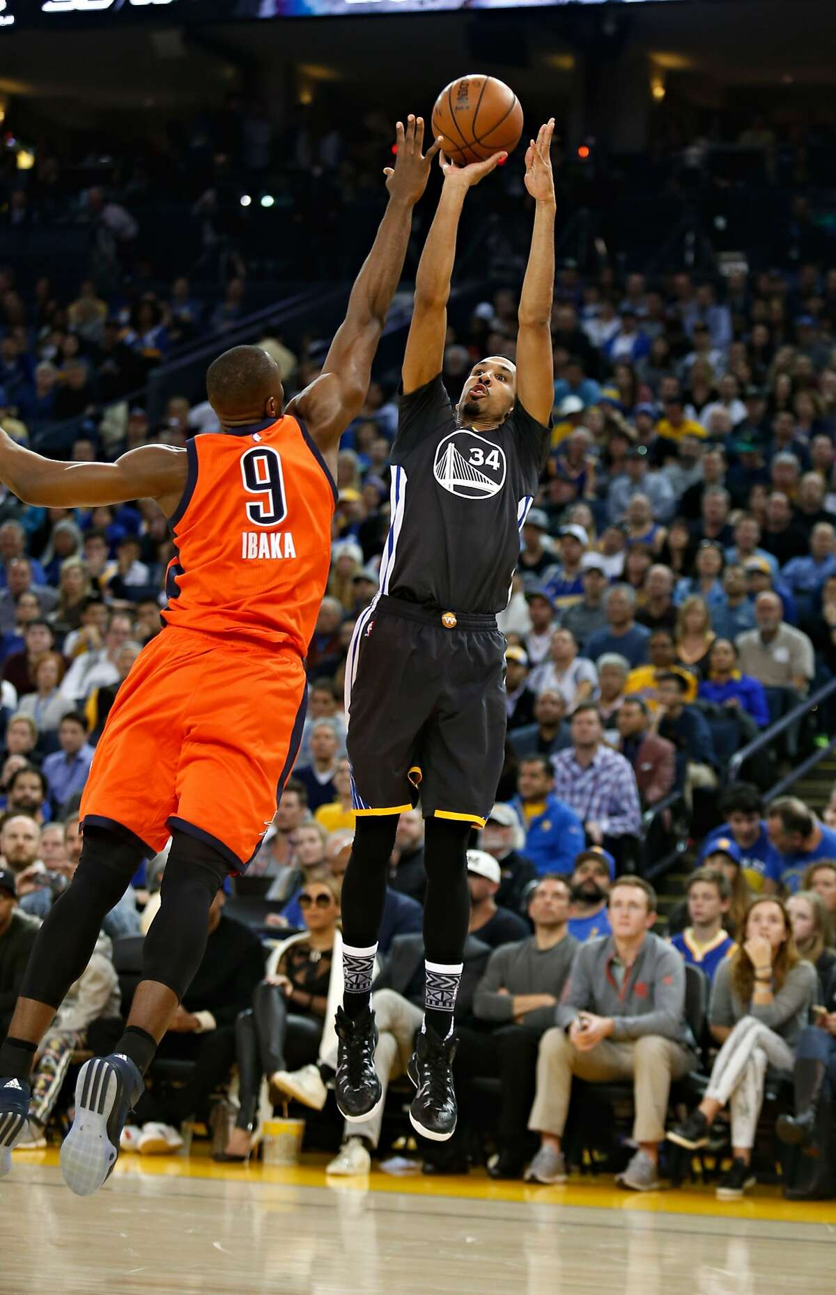 Golden State Warriors guard Shaun Livingston shoots a three pointer while being fouled by Oklahoma City Thunder forward Serge Ibaka during the second quarter of their basketball game on Saturday, February 6, 2016 in Oakland, Calif.