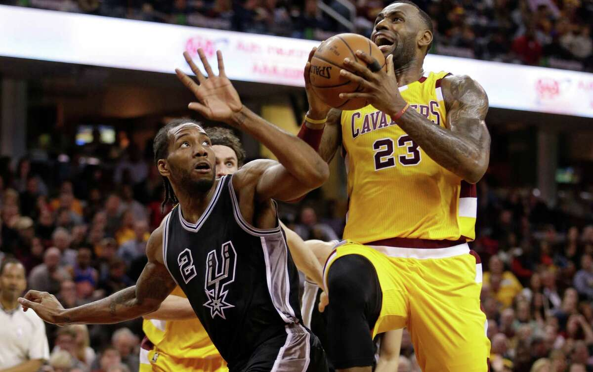 Cavaliers' LeBron James drives to the basket against the Spurs' Kawhi Leonard in the second half on Jan. 30, 2016, in Cleveland.