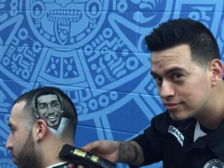San Antonio barber Rob Ferrel works on engraving the likeness of the Spurs' LaMarcus Aldridge into the head of customer Derek Miller. Ferrel owns Rob The Original's Barber Shop.