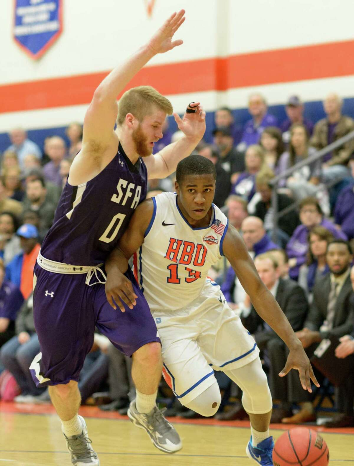 Stephen O'Suji (13) of Houston Baptist University drives to the basket in the first half against the Stephen F. Austin Lumberjacks in a college basketball game on Saturday, February 6, 2016 at Sharp Gym.