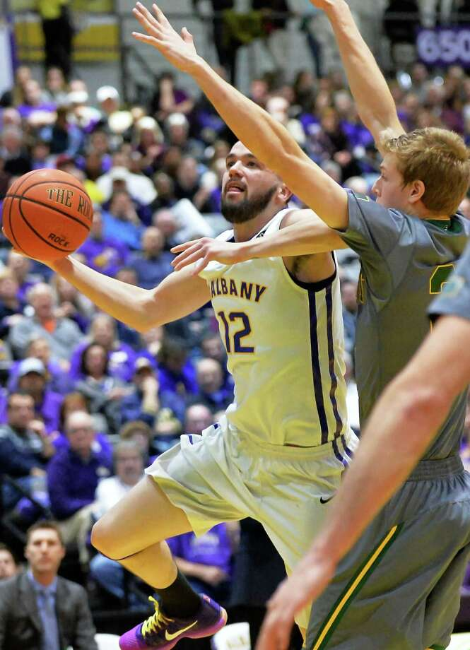 UAlbany's #12 Peter Hooley, left, goes to the basket  against Vermont's #34 Kurt Steidl during Saturday's Big Purple Growl game at the SEFCU Arena Feb. 6, 2016 in Albany, NY.  (John Carl D'Annibale / Times Union) Photo: John Carl D'Annibale / 10035212A