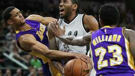 Kawhi Leonard gets fouled by Jordan Clarkson (left) under the hoop as Lou Williams tries to reach in and stop the Spurs forward as the Spurs host the Lakers at the AT&T Center on February 6, 2016.