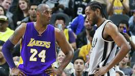 Kobe Bryant looks over Kawhi Leonard coming out of a time out as the Spurs host the Lakers at the AT&T Center on February 6, 2016.