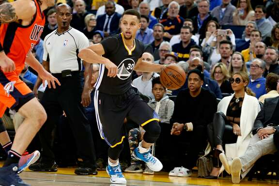 Golden State Warriors guard Stephen Curry dribbles the ball in front of Jay Z and Beyonce during Curry's basketball game against the Oklahoma City Thunder on Saturday, February 6, 2016 in Oakland, Calif.