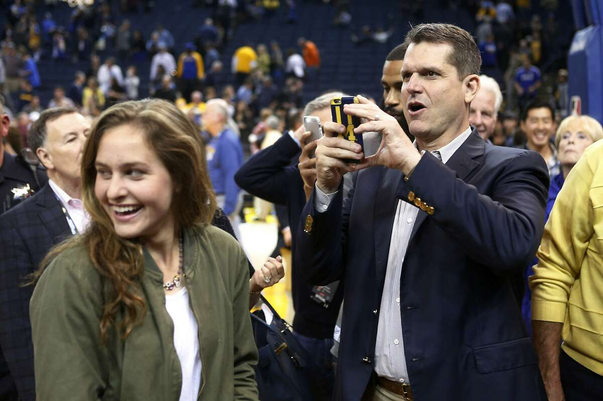 Former 49ers head coach Jim Harbaugh takes photos on his phone after the Golden State Warriors defeated the Oklahoma City Thunder on Saturday, February 6, 2016 in Oakland, Calif.