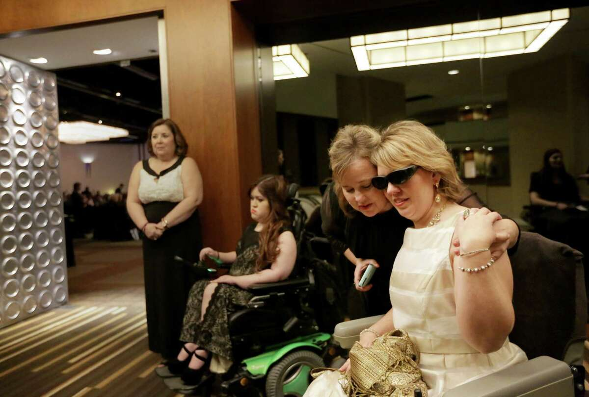 Heather Griffith, right, prays with Amy Norris, second from right, in the hall before the 12th annual Ms. Wheelchair Texas Gala Saturday, Feb. 6, 2016, in Houston.