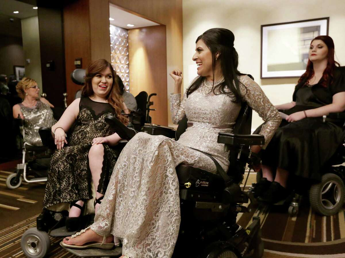 Magui Dunn, second from right, jokes with Marisa Folsom, second from left, as Katy Hayes, left, and Nicole Sheridan, right, wait in the hall before the 12th annual Ms. Wheelchair Texas Gala Saturday, Feb. 6, 2016, in Houston.