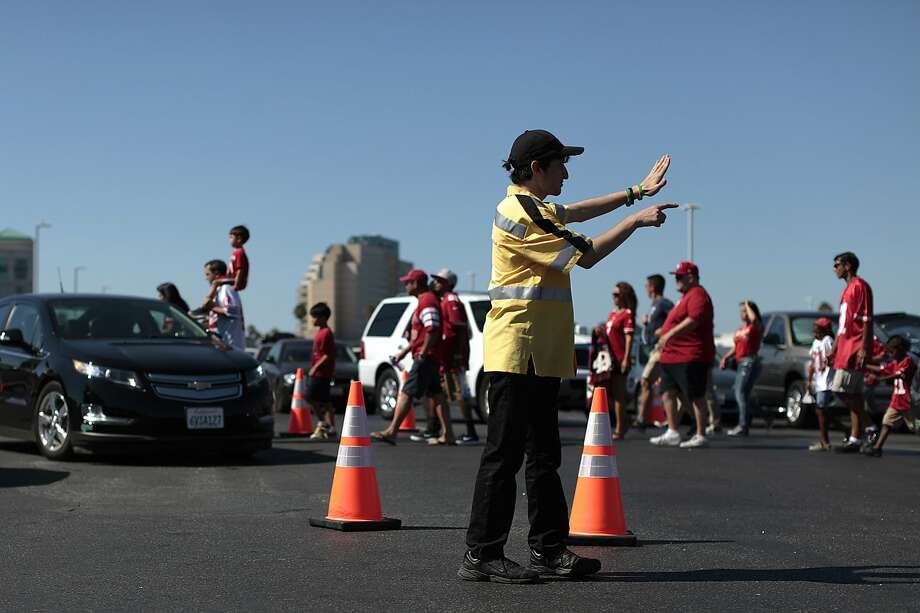 A parking attendant directs traffic after a 49ers game at the Levi's Stadium in August 2014. Photo: James Tensuan, The Chronicle