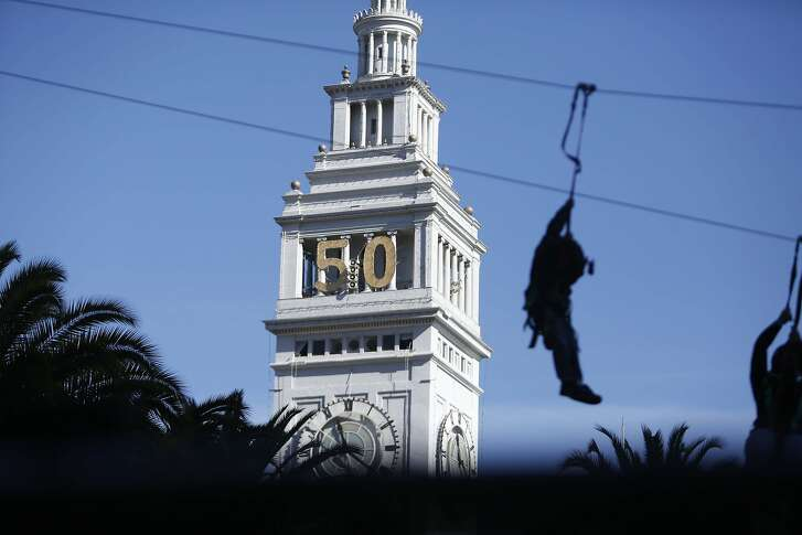 A visitor to Super Bowl City goes down a zip line as the Ferry Building is seen in the background at Super Bowl City on Sunday, February 7, 2016 in San Francisco, Calif.