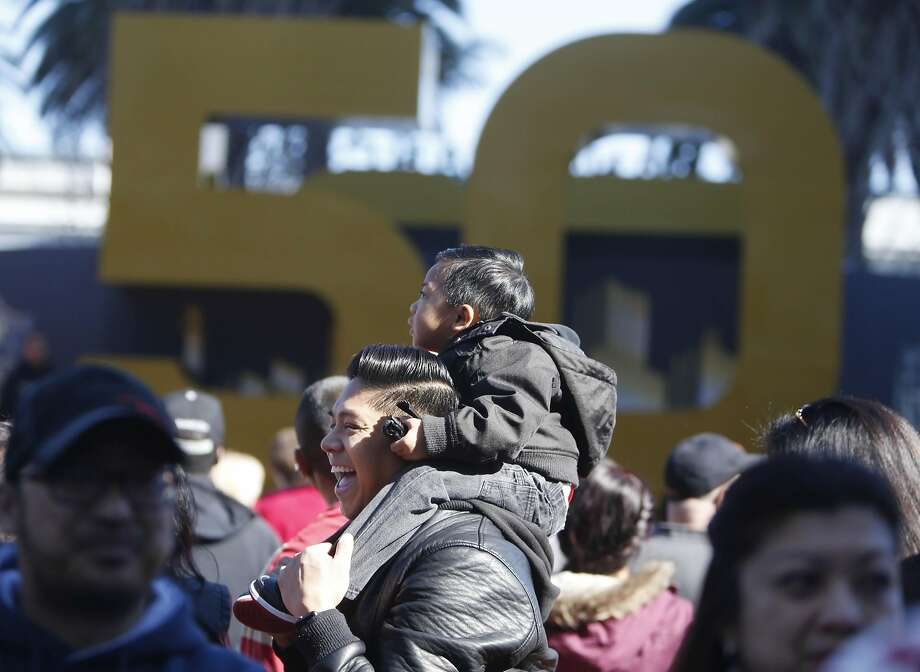 John Eric Gabagat holds his son James Gabagat, 2, on his shoulders as they wait in line to take a photo at Super Bowl City on Sunday, February 7, 2016 in San Francisco, Calif. Photo: Lea Suzuki, The Chronicle