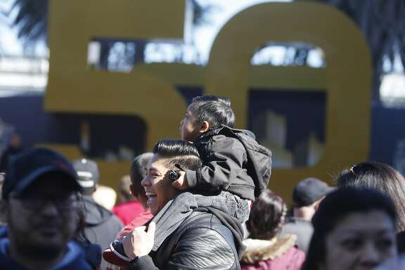 John Eric Gabagat holds his son James Gabagat, 2, on his shoulders as they wait in line to take a photo at Super Bowl City on Sunday, February 7, 2016 in San Francisco, Calif.