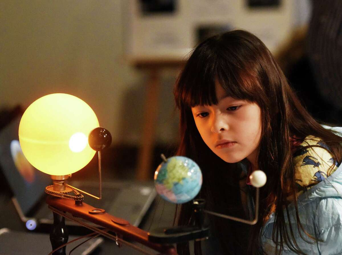 Mika Dunne, 8, of Cos Cob, looks at a demonstration of planetary movement around the sun during Astronomy Family Day at the Bruce Museum in Greenwich, Conn. Sunday, Feb. 7, 2016. The annual event, held by the Astronomical Society of Greenwich, featured a show inside the inflatable Starlab planetarium, telescope demonstrations, discussions on celestial happenings and scientific explanations from knowledgable members of the Astronomical Society.