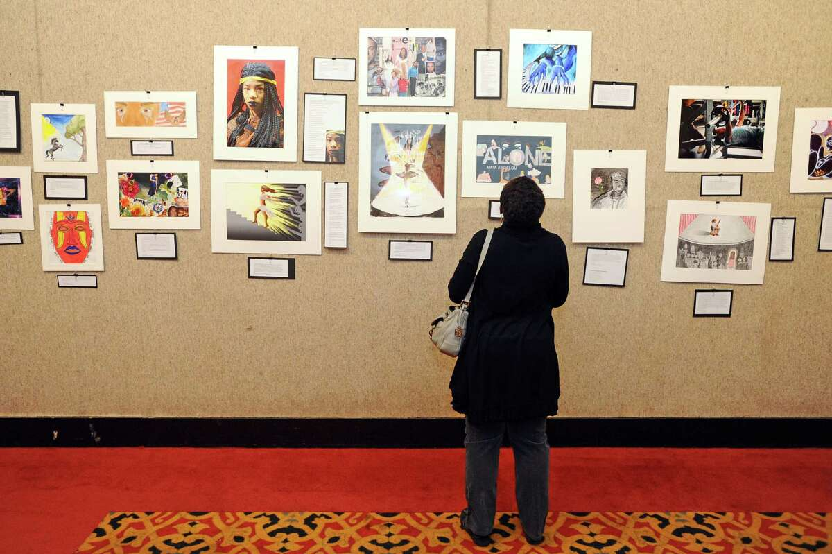 Stamford resident Michelle Phillips looks at the various artwork on display at the Community Art Reception at the Palace Theater on Sunday, Feb. 7, 2016. Stamford's public schools participated in Black History Month with the gallery and had precisely 100 pieces of art available to view.