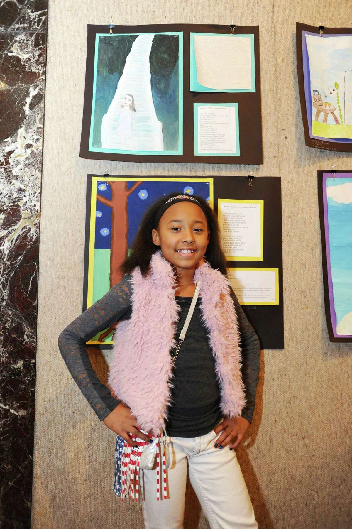 Eleven-year old Heaven Robinson, from Toquam Magnet Elementary School, poses in front of her piece of art. Stamford's public schools participated in Black History Month with a Community Art Reception on Sunday, Feb. 7, 2016 at the Palace Theater in downtown Stamford.