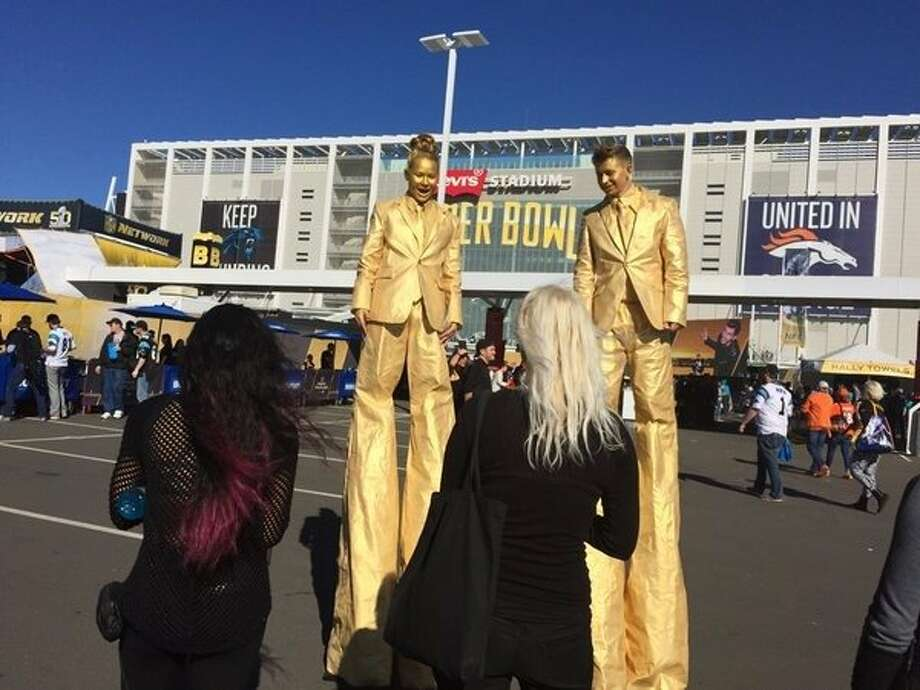 Lo Yee and Tanner Markley, in gold, talk to mere mortals from their stilts at the Super Bowl pre-game festivities at Levi's Stadium. Photo: Peter Fimrite
