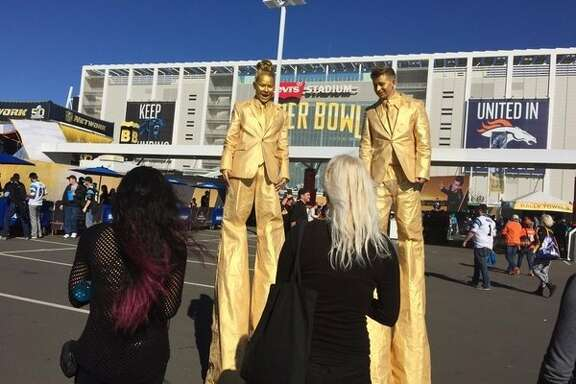 Lo Yee and Tanner Markley, in gold, talk to mere mortals from their stilts at the Super Bowl festivities at Levi's Stadium.