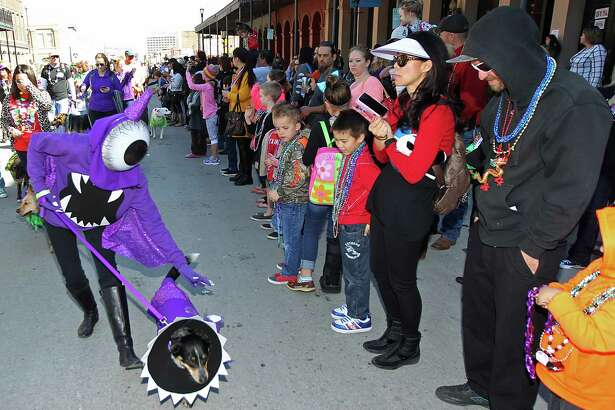 Asha and Britt Thompson, from Houston, dressed as the One Eye Purple People Eater parade on Sunday , February 7, 2016 in the Barkus Parade on the Strand in Galveston, Texas.