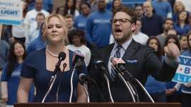 This image provided by Anheuser-Busch shows actors Amy Schumer and Seth Rogen in the company's Bud Light Party campaign spot for Super Bowl 50. (Anheuser-Busch via AP)