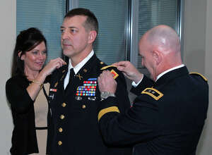 Division of Military and Naval Affairs Christy Johnston, and Maj. Gen. Brian J. McKiernan, commanding general of First Army Division East, right, attach colonel shoulder boards on Kevin L. Johnston?s uniform during a ceremony.