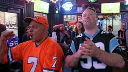 Denver Broncos fan Ben Castro (left) cheers his team as Carolina Panthers fan Justin Harshner looks on while watching the Super Bowl Sunday Feb. 7, 2016 at The Ticket Sports Pub.