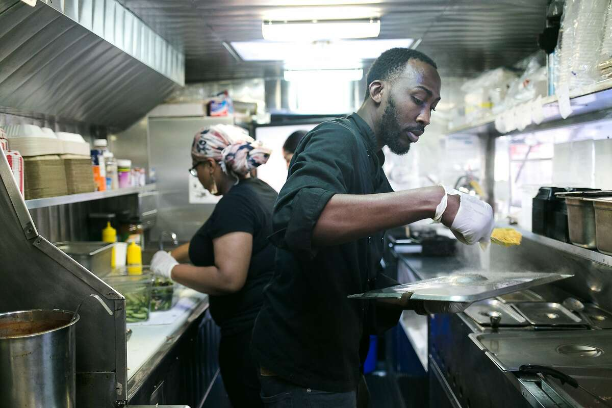 Obrian Matterson and Maritza Butler work in the tight space of the Scotch Bonnet food truck in S.F.