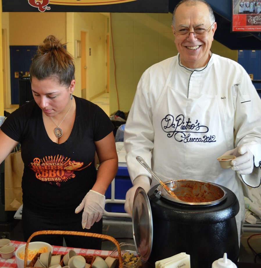 Side-by-side comeptitiors at MacChilifest woo tasters Sunday: Mackenzie Cohane, left, of Bobby Q's served up mac 'n' cheese, while Peitro Scotti offered chili from his restaurant, da Pietro's. Photo: Westport News, Jarret Liotta / Westport News