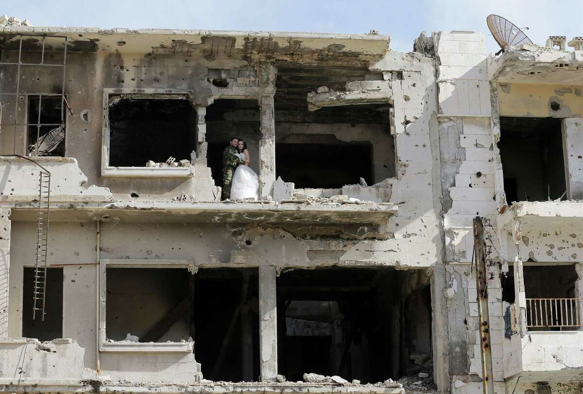 Newly-wed Syrian couple Nada Merhi, 18, and Syrian army soldier Hassan Youssef , 27, pose for a wedding picture amid heavily damaged buildings in the war ravaged city of Homs on February 5, 2016.