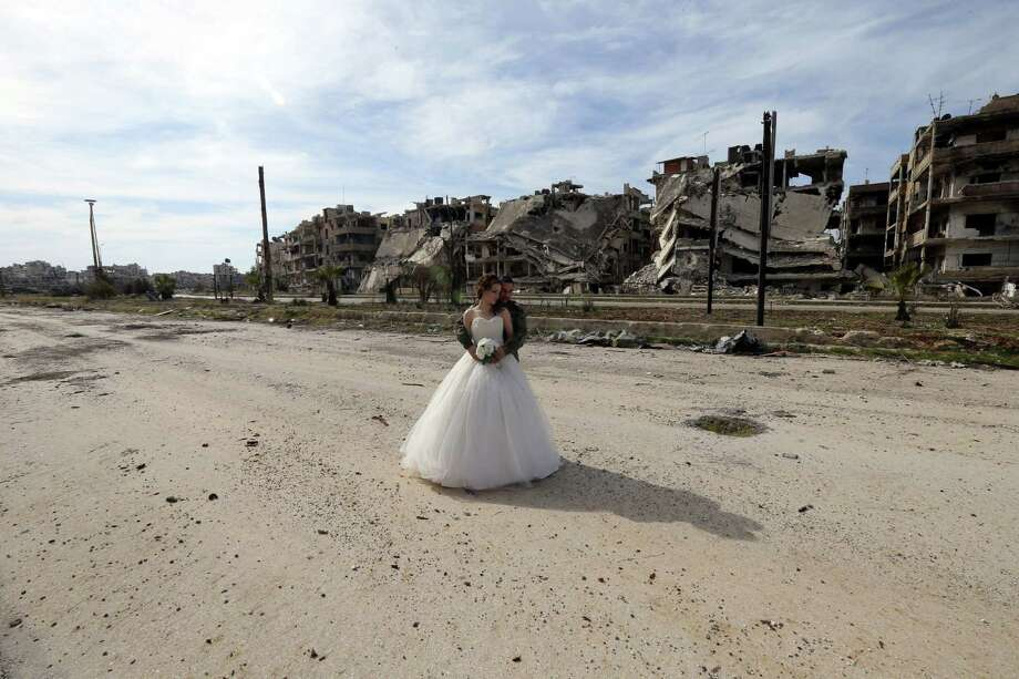 Newly-wed Syrian couple Nada Merhi,18, and Syrian army soldier Hassan Youssef,27, pose for a wedding picture amid heavily damaged buildings in the war ravaged city of Homs on February 5, 2016. A Syrian photographer thought of using the destruction of Homs to take pictures of newly wed couples to show that life is stronger than death.   / AFP / JOSEPH EID Photo: JOSEPH EID, Getty Images / AFP