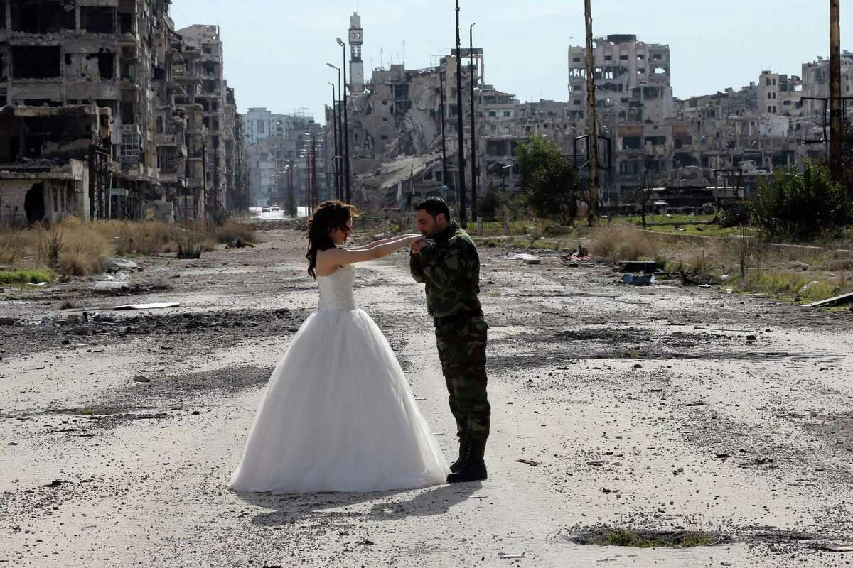 Newly-wed Syrian couple Nada Merhi, 18, and Syrian army soldier Hassan Youssef , 27, pose for a wedding picture amid heavily damaged buildings in the war ravaged city of Homs on February 5, 2016. A Syrian photographer thought of using the destruction of Homs to take pictures of newly wed couples to show that life is stronger than death.