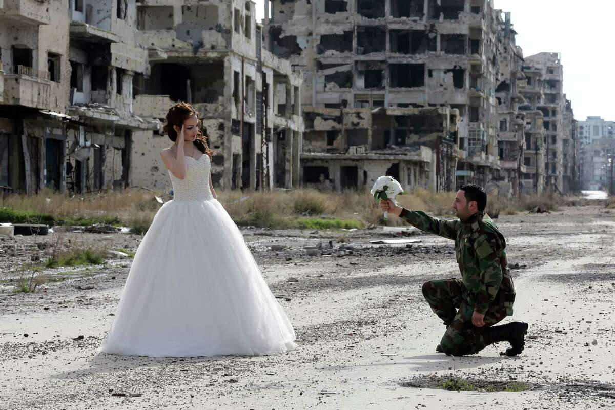 Newly-wed Syrian couple Nada Merhi, 18, and Syrian army soldier Hassan Youssef, 27, pose for a wedding picture amid heavily damaged buildings in the war ravaged city of Homs on February 5, 2016.