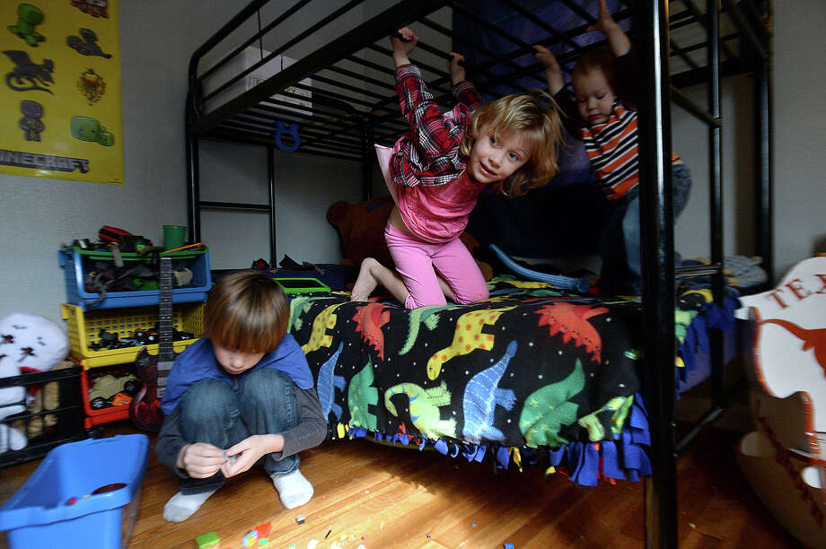 """Charlie Mullin, 8, and siblings Mirren, 5, and Spencer, 1, play in his room at their family home north of Beaumont. After kindergarten, Heather Mullin decided to home school her son, who was often bored with repetitive lessons and activities in the classroom. He is now """"unschooled,"""" and is an integral part of structuring his own learning activities and interests. Plans to create an alternative school based on the self-directed learning methodology is in the works among like minded parents in the area.  Photo taken Wednesday, January 27, 2016  Kim Brent/The Enterprise Photo: Kim Brent / Beaumont Enterprise"""