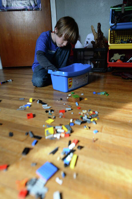 """Charlie Mullin, 8, concocts a legos figure while working in his room at their family home north of Beaumont. After kindergarten, Heather Mullin decided to home school her son, who was often bored with repetitive lessons and activities in the classroom. He is now """"unschooled,"""" and is an integral part of structuring his own learning activities and interests. Plans to create an alternative school based on the self-directed learning methodology is in the works among like minded parents in the area.  Photo taken Wednesday, January 27, 2016  Kim Brent/The Enterprise Photo: Kim Brent / Beaumont Enterprise"""