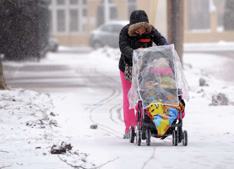 A woamn pushes a stroller through the wind and snow in Bridgeport, Conn. on Monday, Jan. 8, 2016. A winter weather advisory for the area will remain in effect until 6 p.m., with predicted snowfall totals of 3 to 6 inches. There is a slight chance of more snow after 10pm. Photo: Cathy Zuraw, Hearst Connecticut Media / Connecticut Post