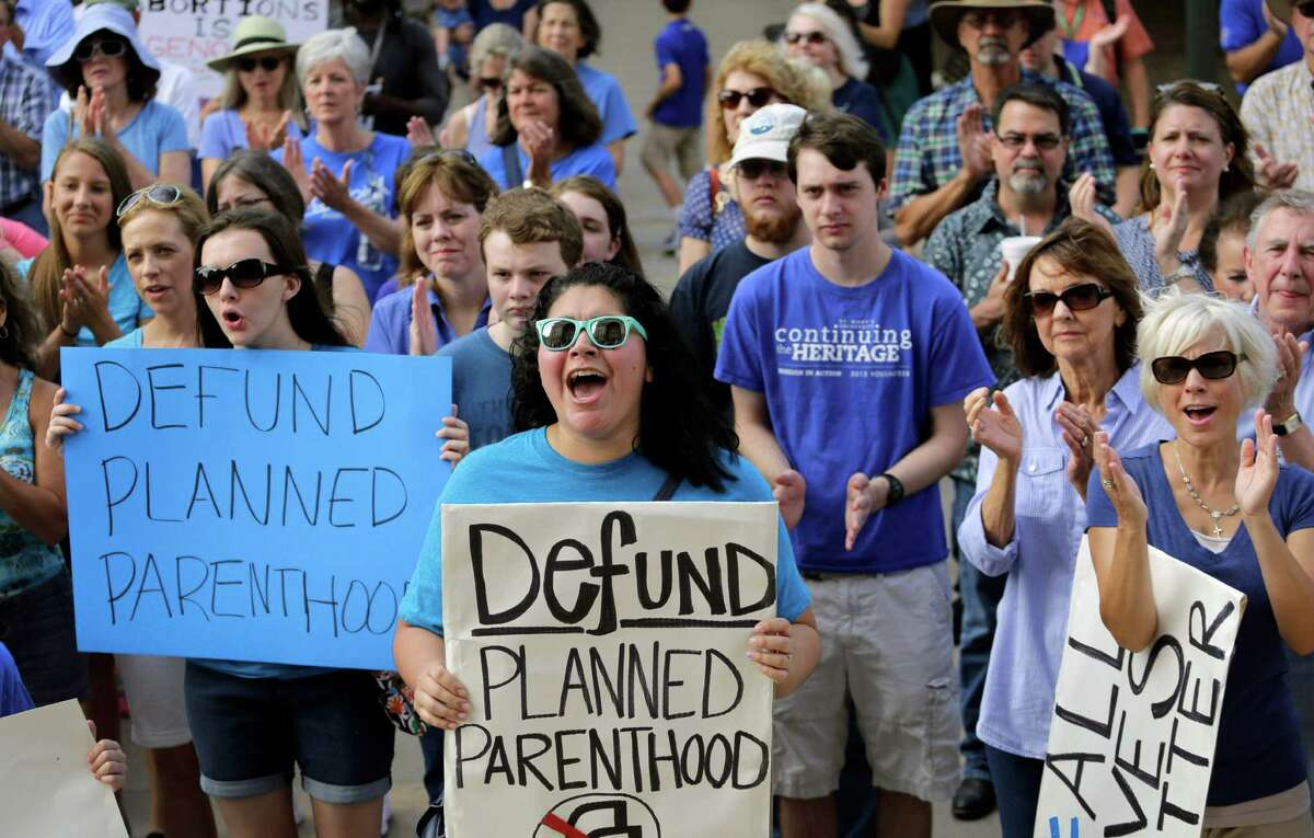 In this July 28, 2015, file photo, Erica Canaut, center, cheers as she and other anti-abortion activists rally on the steps of the Texas Capitol in Austin, Texas, to condemn the use in medical research of tissue samples obtained from aborted fetuses. Texas announced Monday, Oct. 19, 2015, that it was cutting off Medicaid funding to Planned Parenthood clinics following undercover videos of officials discussing fetal tissue, potentially triggering a legal fight like the one unfolding in neighboring Louisiana. (AP Photo/Eric Gay, File)