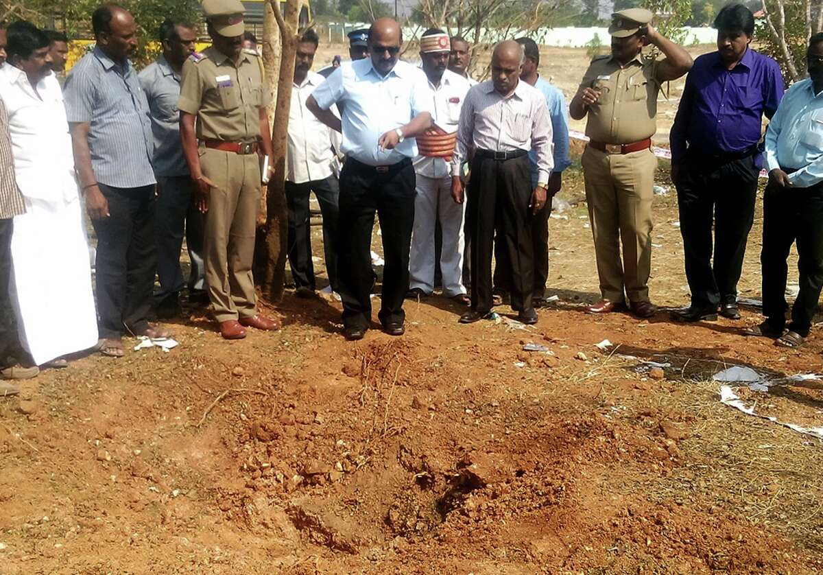 Indian authorities inspect the site of a suspected meteorite landing on February 7, 2016 in Vellore district in southern Tamil Nadu state in an impact that killed a bus driver and injured three others on February 6.