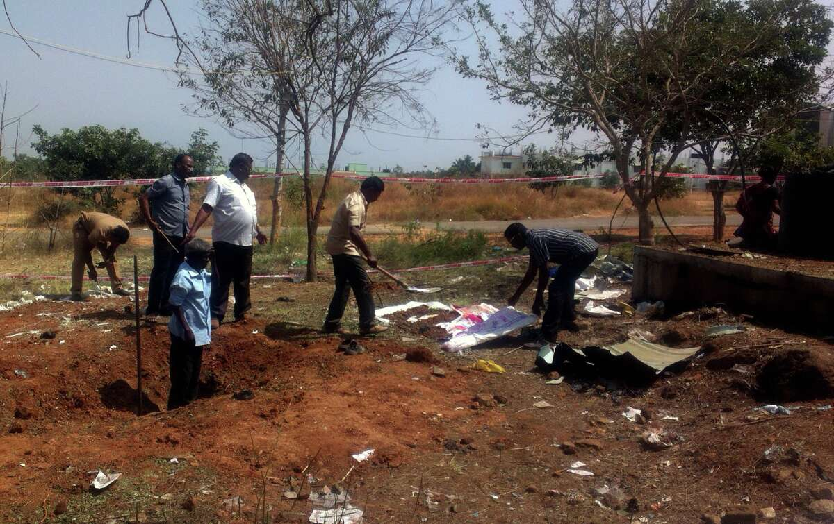 Indian authorities inspect the site of a suspected meteorite landing on February 7, 2016 in Vellore district in southern Tamil Nadu state in an impact that killed a bus driver and injured three others on February 6. If proven, it would be the first such death in recorded history. The impact of the object left a large crater in the ground and shattered window panes in a nearby building, killing the driver who was walking past.