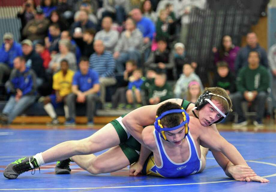 New Milford's CJ Schultz, top, and Newtown's Anthony Piazza wrestle in a 138-pound match at the New Fairfield Duals Saturday at New Fairfield High School. Photo: H John Voorhees III / Hearst Connecticut Media / The News-Times