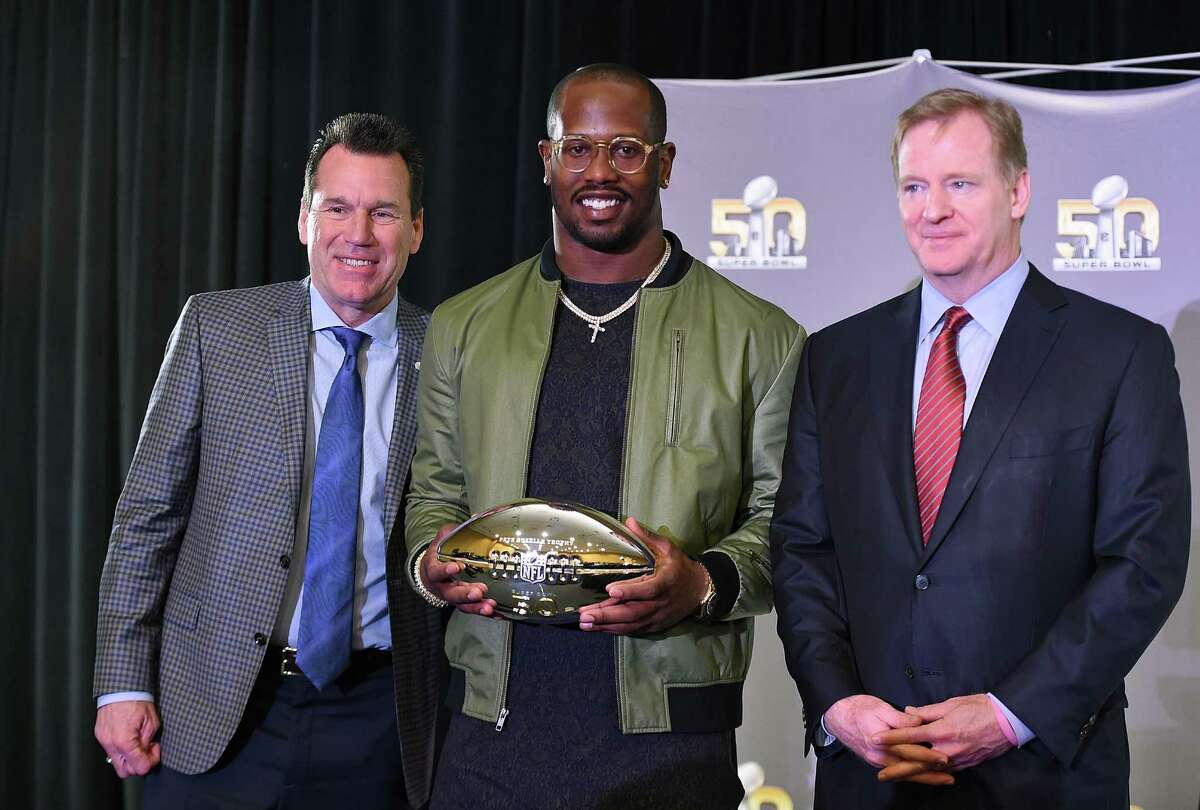 Head coach Gary Kubiak of the Denver Broncos (L) and NFL commissioner Roger Goodell (R) poses with the Super Bowl 50 MVP Von Miller holding the trophy at the Moscone Center West on Monday in San Francisco.